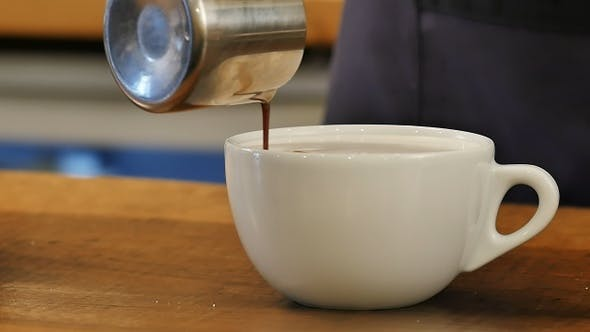 Thumbnail for Pouring coffee into cup with milk
