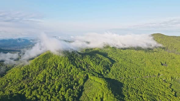 Aerial Flight Flight Over the Top of a Mountain Covered with Clouds