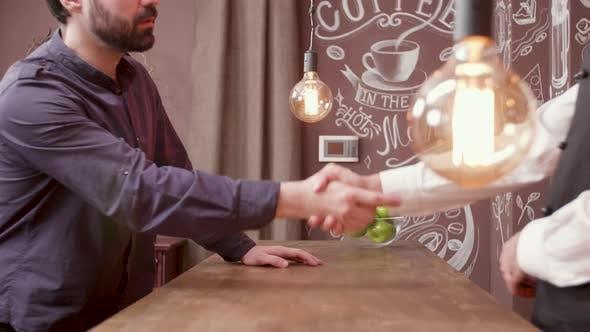 Thumbnail for Young Man Greeting the Bartender and Sits at a Bar Counter