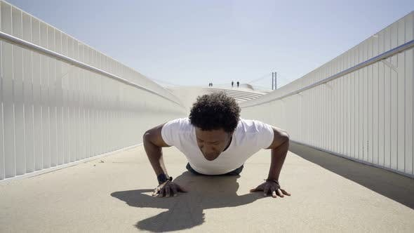 Thumbnail for Focused Sporty Young Man Doing Push-ups on Bridge