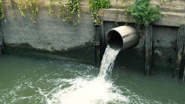 Thumbnail for Wastewater flows down from sewer pipe and pollutes water in river at downtown