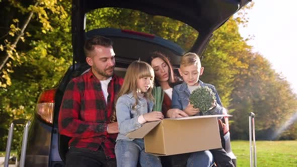 Thumbnail for Smiling Satisfied Parents with Their Nice Children Sitting in the Auto's Trunk