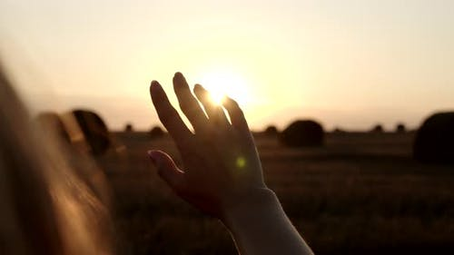 A Woman's Hand Obscures The Setting Sun