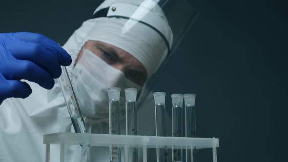 Scientist or Medical in Protective Kit Holding Test Tube with Reagent. Laboratory Glassware