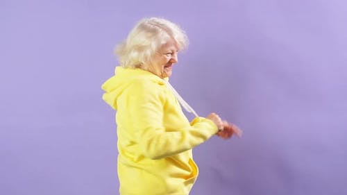 Stylish Granny in a Yellow Sports Sweatshirt Moving To Music, Dancing Party, Style