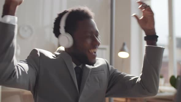 Thumbnail for Happy Afro-American Businessman in Headphones Listening to Music at Work