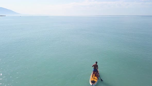Man practicing stand up paddle or SUP