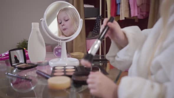 Thumbnail for Little Blond Caucasian Girl Applying Face Powder. Pretty Child in White Bathrobe Standing in Front