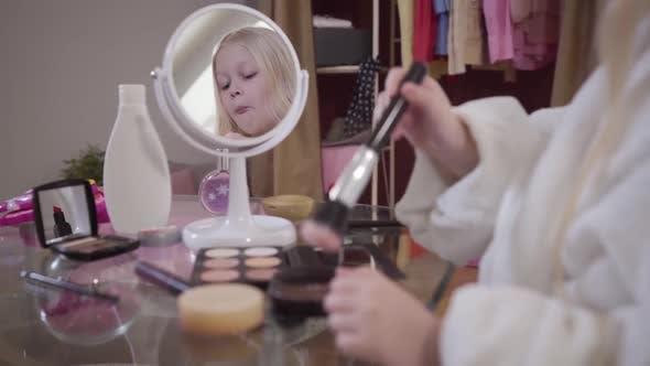 Thumbnail for Little Blond Caucasian Girl Applying Face Powder. Pretty Child in White Bathrobe Standing in Front