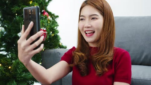 Young Asian female using smart phone video call talking with couple with X'Mas present box