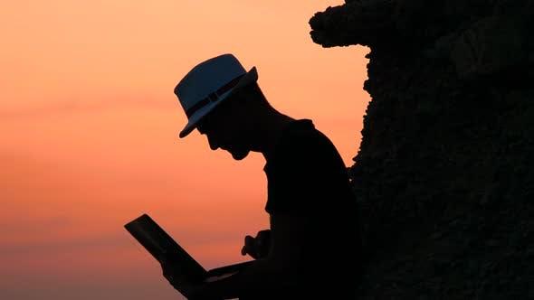 Thumbnail for Attraktiver junger Mann mit Laptop sitzt auf dem Felsen des orangefarbenen Sonnenuntergangs am Meer. Frohe Ferien