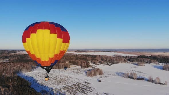 Thumbnail for Aerial Shot of the People Fly on a Big Bright Balloon Over the Winter Forest