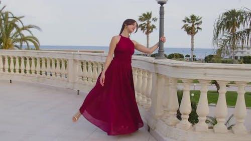 Young beautiful girl in burgundy evening dress