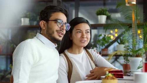 Romantic Diverse Couple Embracing and Talking in Cafe