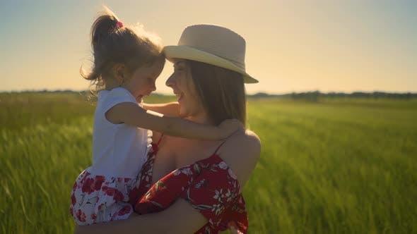 Nahaufnahme: Junge Mutter, Hut tragen, hält kleine Tochter in ihren Armen, Stehen im Feld, der Wind