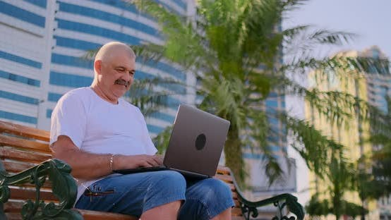 Cover Image for Senior Man in a White T-shirt Sitting in the Park on a Bench Among the Palm Trees and Looking at the
