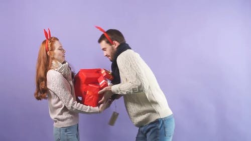 Young Handsome Guy Awkwardly Gives a Variety of Christmas Gifts To His Girlfriend
