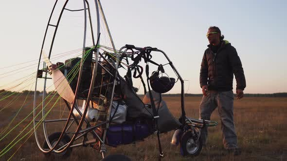 Thumbnail for A Man Pilot of a Motor Paraglider Attaches the Parachute To the Body of the Paraglider Preparing for