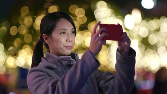 Cover Image for Woman use of mobile phone over golden light blur background