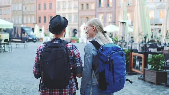View of Tourists Couple with Bags Checking Map on Central City Square