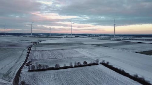 Droneflight moody sky with wind turbines in nature