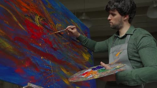 Man is an Artist Holding a Brush and Drawing an Abstract Picture