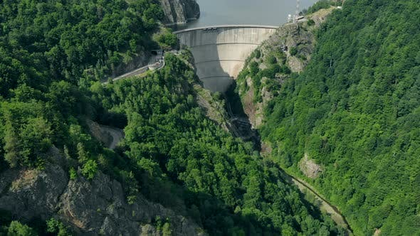 Aerial View of a Hydroelectric Dam in the Mountains Covered with Forest