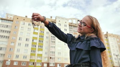 A Young Schoolgirl Holds the Keys to a New Apartment