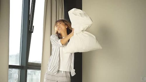 Cheerful Japanese Woman Enjoys the Weekend Waking Up in the Morning a Woman in Pajamas Has Fun in