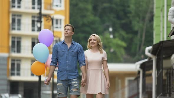 Thumbnail for Girlfriend and Boyfriend with Balloons Walking Down Street, Stopping to Kiss