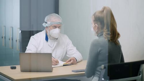 Modern Private Clinic Young Female at a Doctor's Appointment Adult Man Doctor and a Young Woman in
