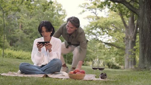 Young People Using Telephone on Picnic