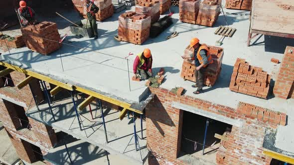 Aerial View Builders Working on Construction and Laying Bricks