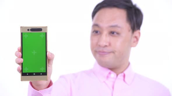 Cover Image for Face of Happy Japanese Businessman Showing Phone