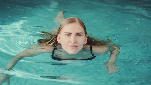 Close Up of Stunning Blonde Woman Swimming in Pool to the Camera