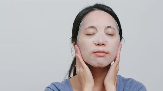 Thumbnail for Junge Frau gelten Gesichtsmaske auf Gesicht zu Hause