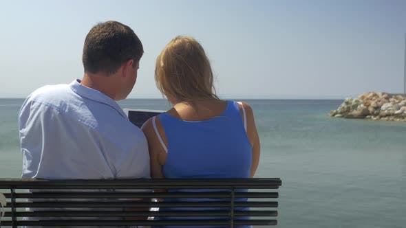 Thumbnail for Young Woman and Man Are Sitting on Bench on Beach on Sea Skyline Background Watching Something in