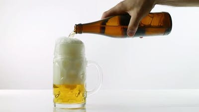 Pouring Beer Into A Beer Glass From A Glass Bottle On A White Background, Fresh Beer Is Pouring.