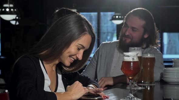 Thumbnail for Beautiful Happy Woman Using Her Smart Phone, Drinking Beer with Friends