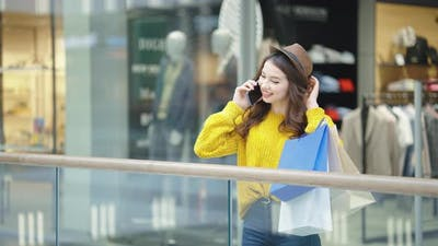 Woman with Purchases Talking on Phone