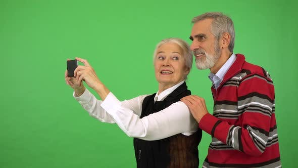 Thumbnail for An Elderly Couple Takes a Picture of Something Off the Camera with a Smartphone