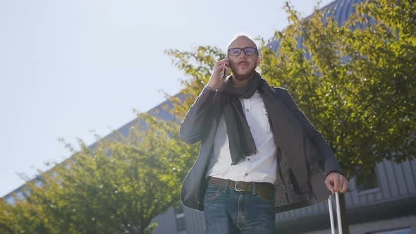 Thumbnail for Young bearded businessman dressed in jacket is talking on phone