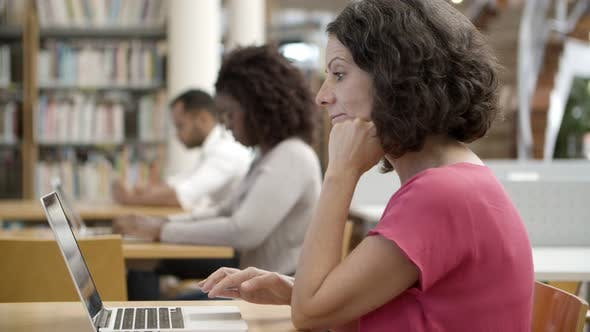 Thumbnail for Side View of Thoughtful Mature Woman Using Laptop