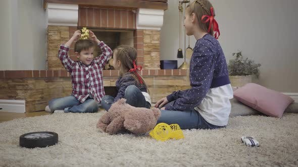 Thumbnail for Portrait of Cheerful Caucasian Boy Putting Toy Crown on Head Entertaining Elder and Younger Sisters