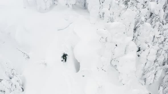Thumbnail for Aerial Drone Shot Above Snowboarder Hiking Up Mountain In Deep Powder Snow at Ski Resort