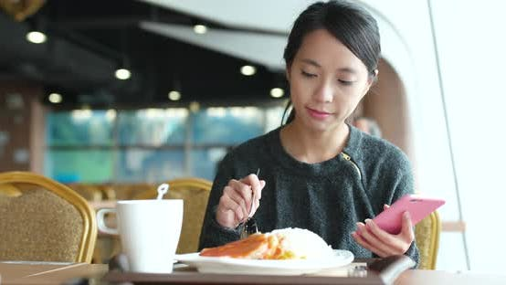 Thumbnail for Busy woman use of mobile phone with her lunch