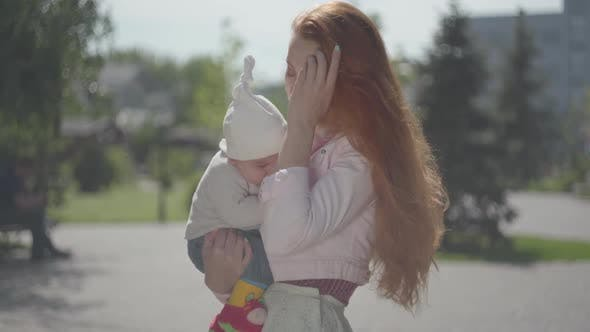 Thumbnail for Young Beautiful Redhead Mother Holding a Cute Baby in Her Arms and Talking To Him in a Spring Sunny