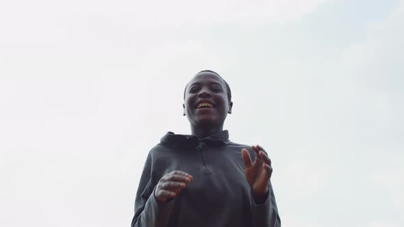 African woman jumping and clapping hands