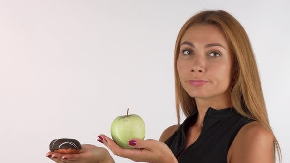 Thumbnail for Young Woman Looking Confused Choosing Between Healthy and Junk Food
