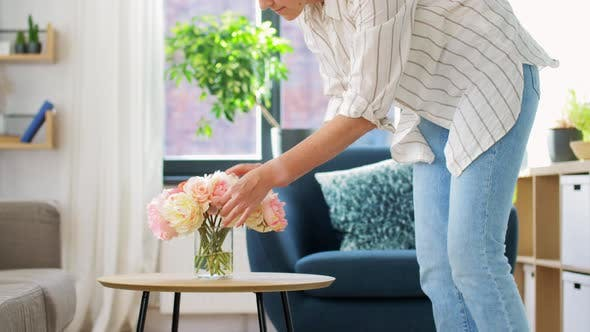 Thumbnail for Woman Placing Flowers on Coffee Table at Home
